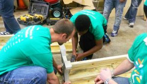 Big Brother Cory builds a bench to beautify a local school as part of Comcast Cares Day
